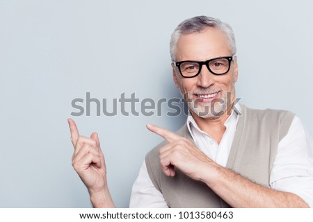 Follow me! Look here! Close up portrait of cheerful satisfied pleased qualified experienced joyful grandfather pointing on empty blank place over shoulder beige waistcoat isolated on gray background