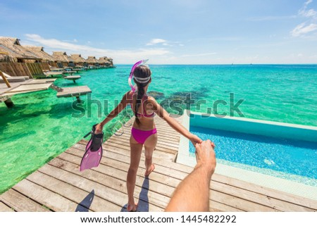 Follow me luxury travel vacation couple following woman snorkeling at overwater bungalow hotel. Man holding hand following woman in Bora Bora, Tahiti, French Polynesia. Watersport fun activity. #1445482292