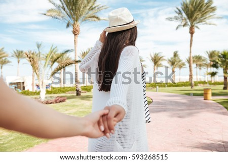 Follow me. Pretty young woman in hat holding hand and leading her friend on summer resort #593268515