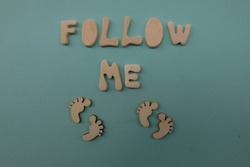Follow me text composed with handmade wooden letters and feet