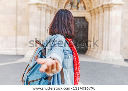 Follow me to Matthias church in Budapest. Mixed race woman traveler with backpack heading to tourist sights and destinations in Europe #1114016798