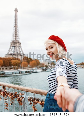 Follow me to Paris. Travel, tourism, advertising concept. Beautiful happy smiling lady wearing red beret, striped t-shirt holds her boyfriend by hand and walks on bridge with view of Eiffel tower