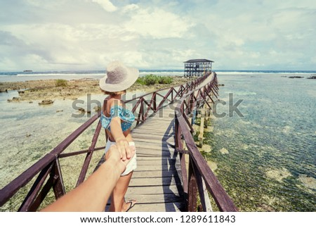 Follow me. Travel concept. Vacation on tropical island. Back of young woman in hat holding boyfriend's hand enjoying sea view from wooden bridge terrace, Cloud 9 Surfing Spot, Siargao Philippines.