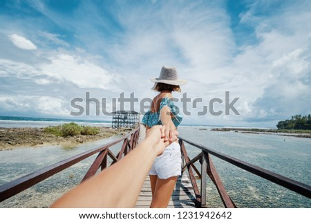 Follow me. Travel concept. Vacation on tropical island. Back view young woman in hat holding boyfriend's hand enjoying sea view from wooden bridge terrace, Cloud 9 Surfing Spot, Siargao Philippines.
