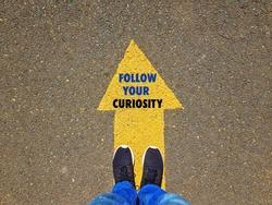 Follow your curiosity on yellow arrow, section of a man standing on yellow arrow on asphalt ground