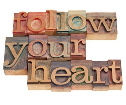follow your heart phrase in vintage wood letterpress type, stained by color inks, isolated on white