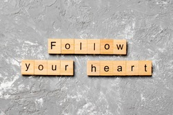 Follow your heart word written on wood block. Follow your heart text on cement table for your desing, Top view concept.