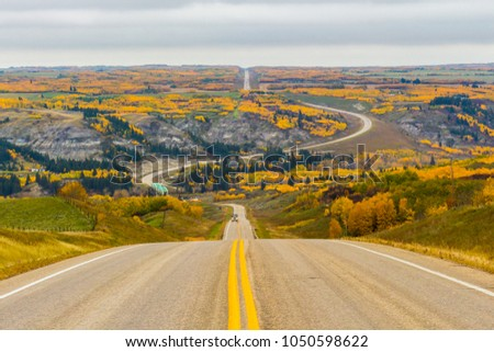 Stock Photo Following a road through a large valley during fall