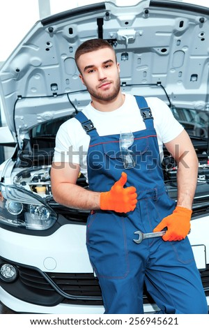 Following my passion to cars. Portrait of a smiling handsome mechanic in uniform posing by the car at car service station holding repair tools