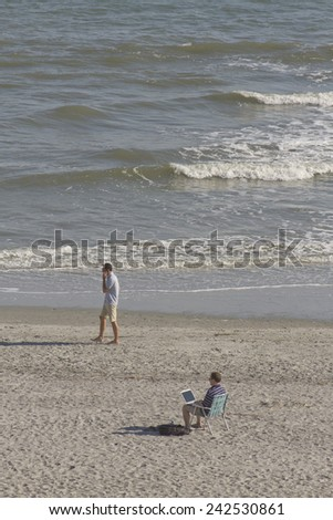 FOLLY BEACH, SOUTH CAROLINA, USA - OCTOBER 23, 2011:    A young man works on his laptop computer and another man walks by talking on a cell phone on a beach with the ocean in the background