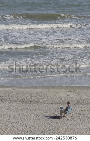 FOLLY BEACH, SOUTH CAROLINA, USA - OCTOBER 23, 2011:    A young man works on his laptop computer while sitting on a beach chair by the sea