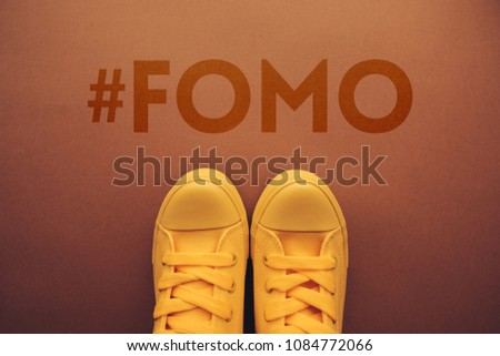 FOMO, fear of missing out concept with yellow sneakers from above.