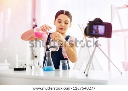 Fond of filming. Beautiful stylish cute schoolgirl fond of filming video blogs making experiment near camera