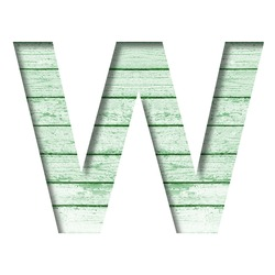 Font on an old wooden wall. The letter W cut out of paper on the background old wood wall with peeled green paint. Set of decorative fonts.