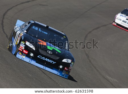 FONTANA, CA - OCT 08, 2010:  Denny Hamlin brings his FedEx Chevrolet through the turns during a practice session for the Pepsi Max 400 race at the Auto Club Speedway in Fontana, CA on Oct 8, 2010.