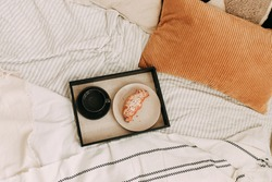 Food a croissant and a cup of coffee on a tray on the bed in a cozy room in the bedroom of the house