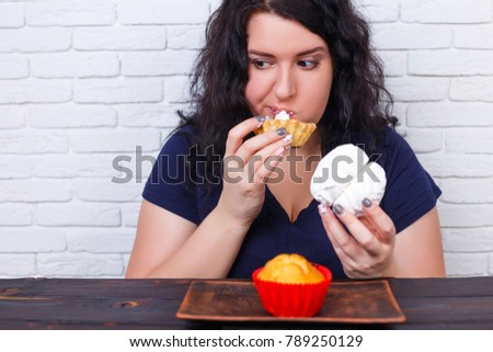 Food addiction, dieting concept. Young overweight woman fed up with diets eating a cake. #789250129