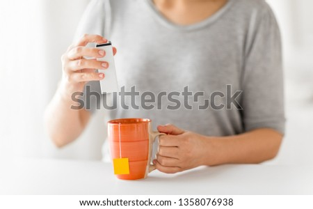food additives and drinks concept - close up of woman adding sweetener to cup of tea
