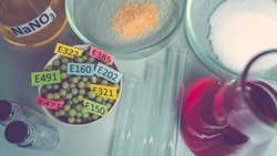 Food additives: chemical additives in the form of granules with colored labels, sodium nitrate in a flask, sugar and glutamate on a laboratory bench. Top view.