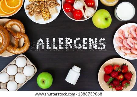 Food allergens as milk, oranges, tomatoes, garlic, shrimp, peanuts, eggs, apples, bread, strawberries on wooden table. Сток-фото ©