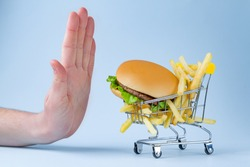 Food and diet concept. French fries and hamburger for snack. Fast food addiction. Fighting overweight and obesity. Refusal of junk, unhealthy food. Restriction in carbohydrate food