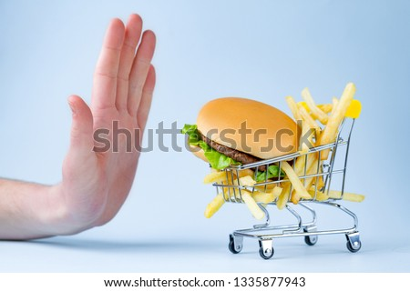 Food and diet concept. French fries and hamburger for snack. Fast food addiction. Fighting overweight and obesity. Refusal of junk, unhealthy food. Restriction in carbohydrate food Foto d'archivio ©