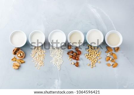 Food and drink, health care, diet and nutrition concept. Assortment of organic vegan non dairy milk from nuts, oatmeal, rice, soy in glasses on a kitchen table. Copy space top view flat lay background