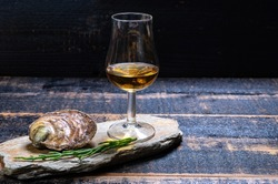 Food and drink pairing, Fresh raw European flat oysters grown in Brittany in Belon river, France, close up and scotch single malt whisky from Islay island, Scotland