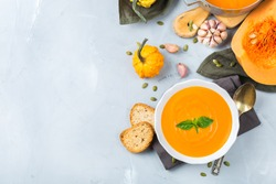 Food and drink, still life, diet and nutrition concept. Seasonal fall autumn roasted orange pumpkin carrot soup with ingredients on a table. Copy space cozy background, top view flat lay