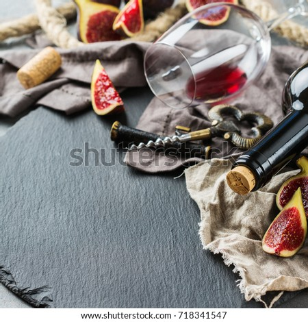 Food and drink, still life, holidays seasonal harvesting fall autumn concept. Bottle, corkscrew, corks, glass of red wine and figs on a grunge table. Copy space background #718341547