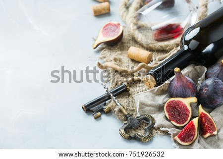 Food and drink, still life, holidays seasonal harvesting fall concept. Bottle, corkscrew, corks, glass of red wine and figs on a trendy concrete table. Copy space background #751926532