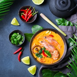 Food and drink, traditional Thai cuisine. Spicy tom yam kung, tom yum sour soup with shrimp, prawn, coconut milk, lemongrass and chili pepper in a bowl on a table