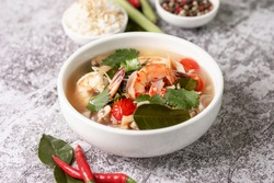 Food and drink, traditional Thai cuisine. Spicy tom yam kung, tom yum sour soup with shrimp, prawn, coconut milk, lemongrass and chili pepper in a bowl