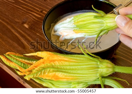 Food And Drinks - Italian Food - Fried zucchini flowers preparation - Closeup of hand passing a zucchini flower in the batter.
