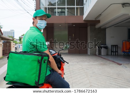 Food and parcels delivery concept. Delivery staff in green uniform with face mask, parking  motorcycle waiting for customers in front of condominium.