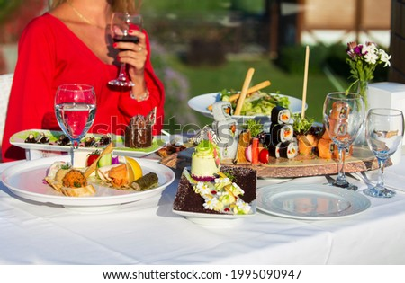 Food and vacation concept. In the depth of field, young woman in red dress holding wine glass.  Suşi ve tatlı tabakları ile, professional food presentation on a white tablecloth. Stok fotoğraf ©