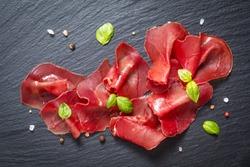 Food appetizer concept Sliced Dried Cured beefs Bresaola on black slate stone board