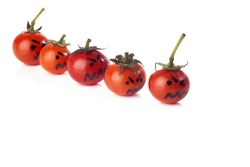 Food art creative concept. Halloween scary faces made of sweet tomatoes like monsters isolated over a white background