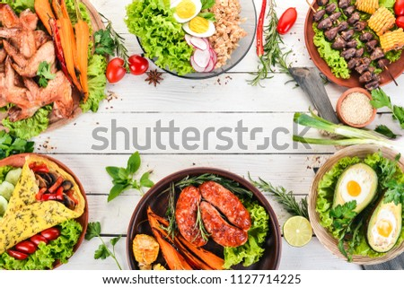 Food. Avocado dishes, chicken wings, omelet and barbecue. On a wooden background. Top view. Copy space.