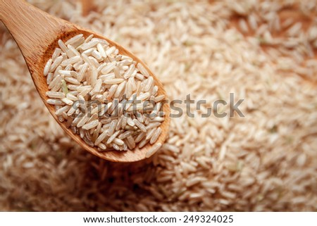 food background. brown rice in a wooden spoon. top view
