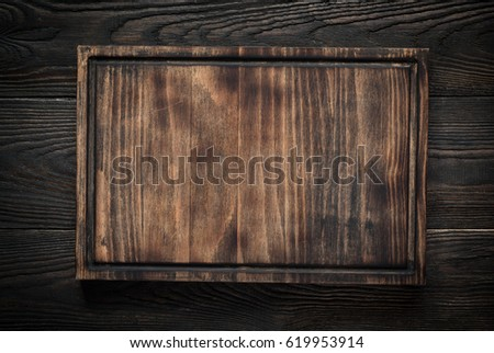 Food background. Cutting board on dark wooden table. Copy space. #619953914