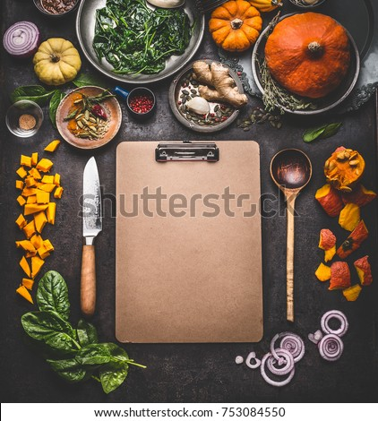Food background for tasty winter and autumn dishes with pumpkin. Various cooking ingredients with spoon and knife around blank cardboard clipboard for menu or recipes , top view, frame, mock up