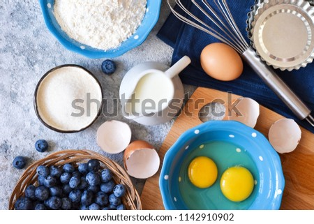 Food background. Ingredients for baking: flour, eggs, berries, chocolate on a concrete background. #1142910902