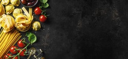Food background. Italian food background with pasta, ravioli, tomatoes, olives and basil on dark background. Horizontal with copy space.