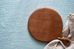 Food background mockup with round wooden cutting board on blue linen textile tablecloth backdrop. Top view, copy space. Menu, recipe, mock up for baking dessert and cupcakes