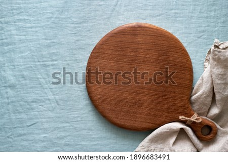 Food background mockup with round wooden cutting board on blue linen textile tablecloth backdrop. Top view, copy space. Menu, recipe, mock up for baking dessert and cupcakes Stockfoto ©