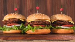 food background of three pieces of hamburgers on wooden board with wooden backdrop