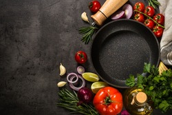 Food background on black slate table. Ingredients for cooking food - tomatoes, onion, spices and herbs with black skillet. Top view with copy space.