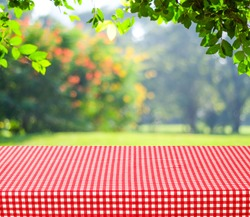 Food background, Picnic table with tablecloth for food, product display over blur green nature outdoor background, Table top, desk cover with white and red pattern clothing and blurred garden