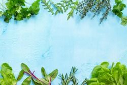 Food background. Various summer green fresh herbs - parsley, lettuce, rosemary, thyme, arugula and spinach on a blue stone table. Copy space, top view flat lay background.